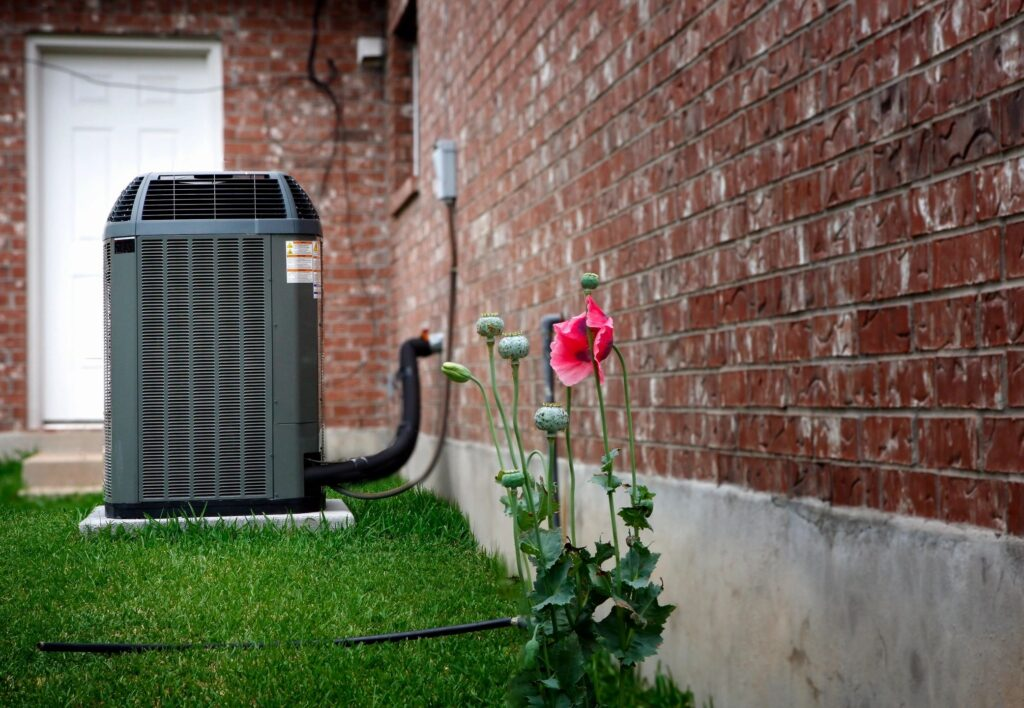 ac unit outside with lawn & flowers